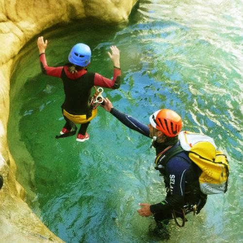 Niña realizando un salto sencillo de 2m en las cristalinas aguas del la Peonera. En la imagen se puede apreciar como el guía protege de las zonas de riesgo y acompaña al participante durante la teyectoria y recepción del salto.