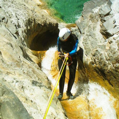 Rapel en el Barranco de Siresa, Pirineo Occidental. En la imagen se aprecia cómo la participante realiza la maniobra asegurada por el guía desde la cabecera.