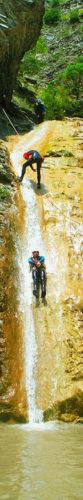Tobogán de 10m al final del Barranco de Siresa, Valle de Echo en Pirineos. El guía de barrancos protege al participante durante el acceso al comienzo del tobogán, y le ayuda para Lanzarse con la trayectoria adecuada.